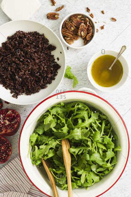 Ingredients in bowls for a rocket, pomegranate and rice salad.