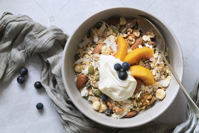 Healthy breakfast; bowl of muesli with sliced peaches and yoghurt.