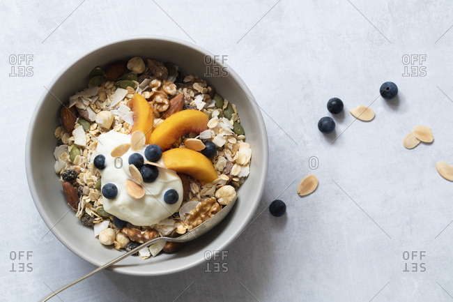 Bowl of homemade muesli with sliced peaches, yoghurt and blueberries.