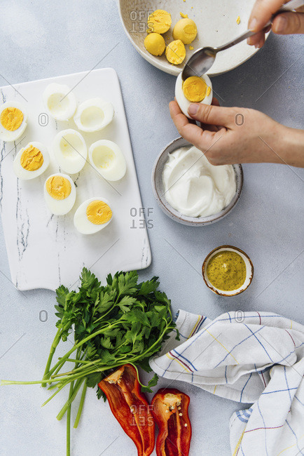 Woman preparing deviled eggs with mustard and greek yogurt on a grey background.
