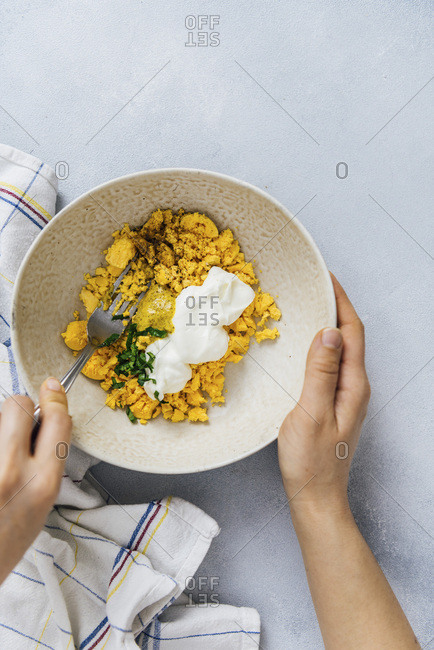 Woman making easter eggs filling with yolks, greek yogurt, parsley and mustard in a bowl with a fork.
