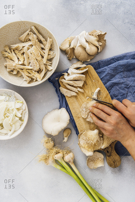 Woman slicing oyster mushrooms on a wooden board. Onions and fresh garlic accompany.