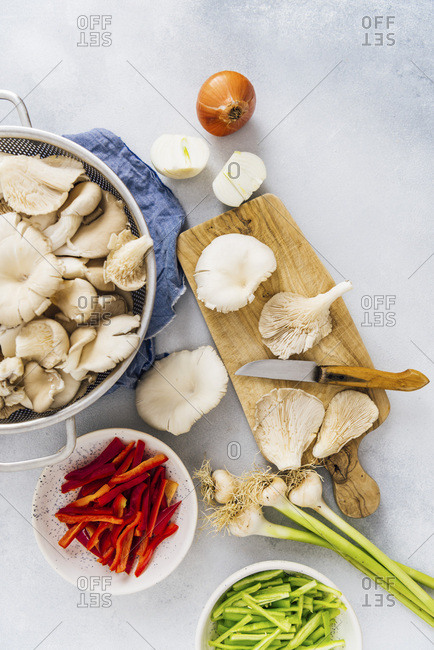 Oyster mushrooms, onions, fresh garlic, red and green bell peppers on a grey background.