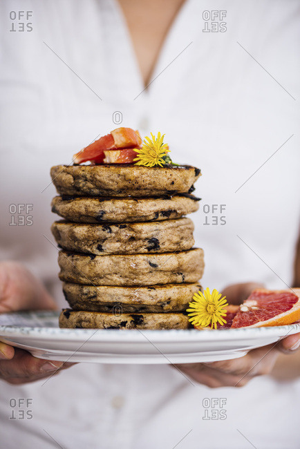 Woman holding a stack of pancakes with chocolate chips on a plate with flowers and grapefruit wedges.