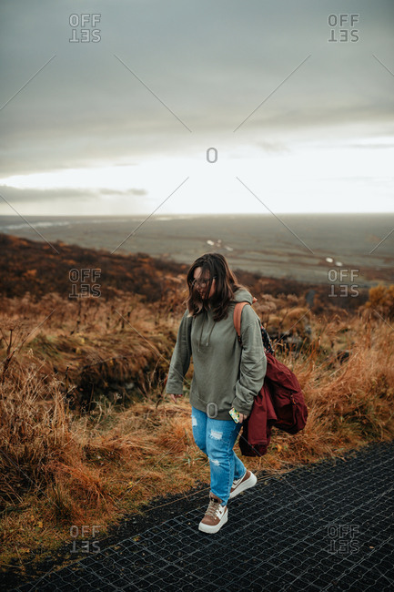 Young female hiker in comfort clothes with backpack walking in desert countryside against grey gloomy sky