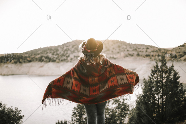 Back view of lady in hat and poncho looking at sunrise sky and mountains while standing on shore of tranquil lake