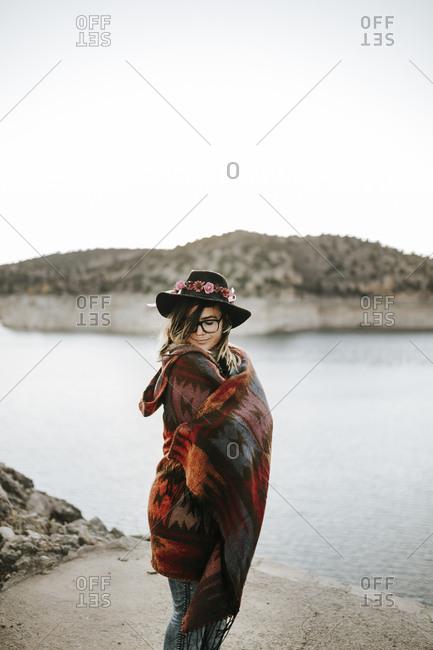 Anonymous woman near calm lake on sunrise