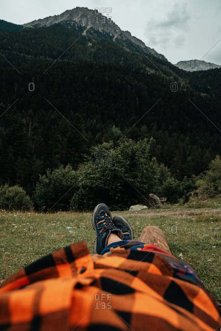 Unrecognizable tourist lying on grass near majestic mountain peak in countryside