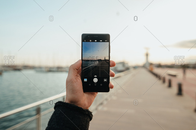Hand of anonymous man using smartphone to take photo of empty embankment in evening