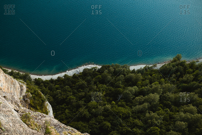 Wonderful view of green forest and calm sea from rocky cliff in beautiful countryside