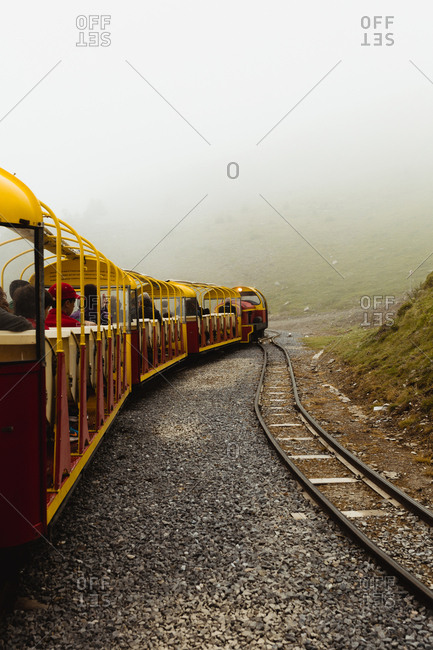 Small train riding on tourist railroad on misty day in amazing countryside