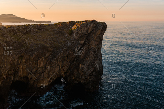 Panoramic view of huge rocky cliffs above rippled water against sunset sky, Asturias, Spain