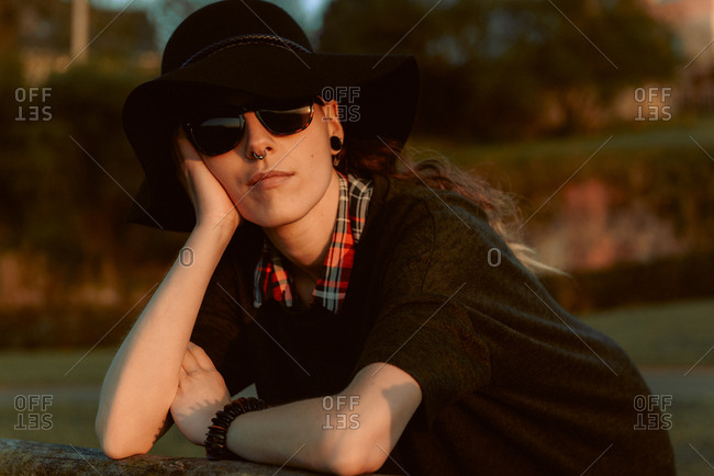 Young sensual brunette wearing black hat and accessories while posing in sunlight with sunglasses