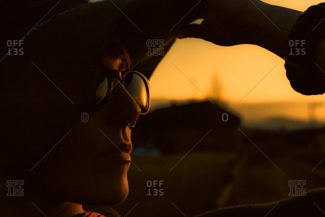 Crop headshot of woman with piercing wearing hat and sunglasses in shadows against sunset sky