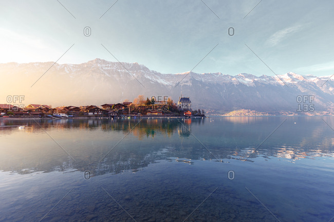 February 16, 2017: Landscape of peaceful blue lake with small pier and boats on background of mountains in sunshine, Switzerland