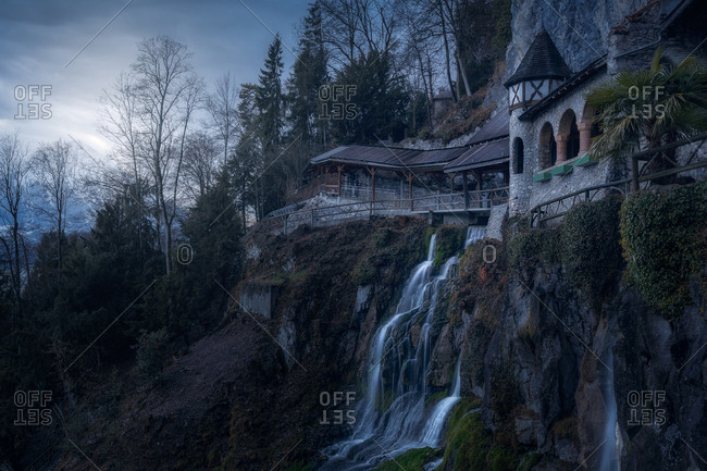 From below of water cascade falling from rocky cliff with building above, Switzerland