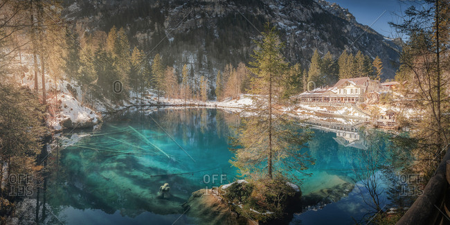 Landscape of peaceful azure lake with snowy shore and resort building in mountains of Switzerland