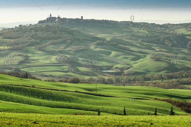 March 22, 2018: Picturesque landscape of green highlands with town in valley, Tuscany, Italy
