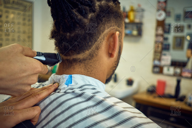 Crop view from behind of Anonymous hairstylist doing a modern haircut with a razor to a faceless African American customer