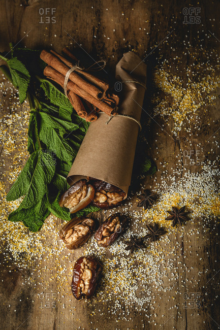 Dates fruits with walnuts, mint and cinnamon Muslim halal snack wrapped in paper for Ramadan