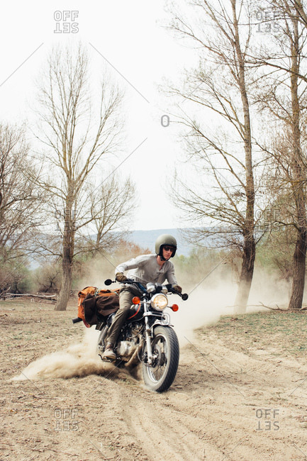 Male in helmet riding fast motorbike on dusty countryside road near leafless trees in nature