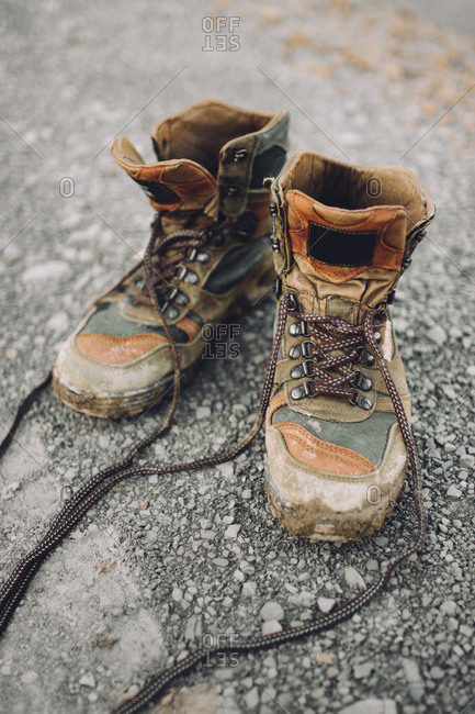 Pair of weathered hiking boots placed on stony road in countryside