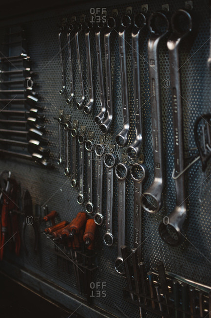 Set of assorted repair tools attached to grungy metal wall in professional workshop