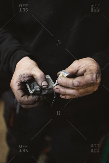 Unrecognizable repairman with dirty hands gluing broken part in workshop