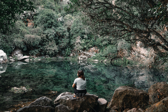 Back view of female traveler sitting on boulders near secret lagoon with calm water in forest in New Zealand