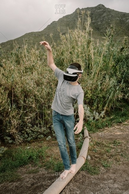 Young adolescent playing a virtual reality simulation with vr glasses and balancing on a pipe tube