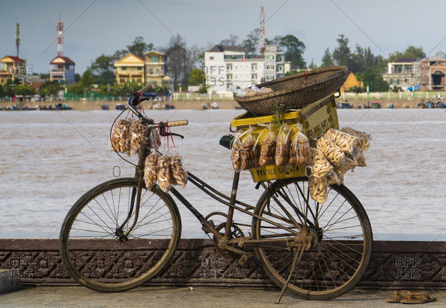 Rusty old bicycle with hanging plastic pockets of food and box against city seashore, Cambodia