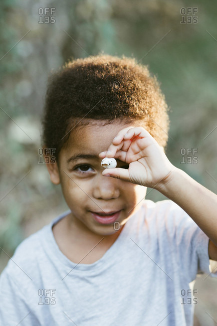 Sweet African American child looking at camera and demonstrating tiny seashell while standing against blurred background in countryside