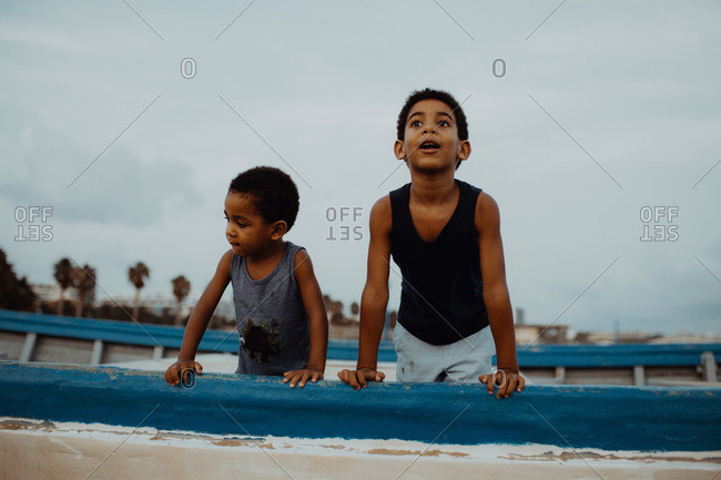 Two astonished African American boys leaning on shabby old vessel and looking away while spending time on beach together