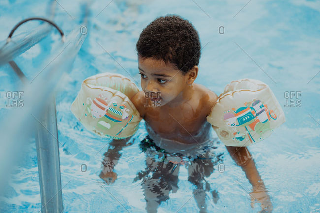 Adorable African American boy in water wings looking away while swimming in clean water of pool
