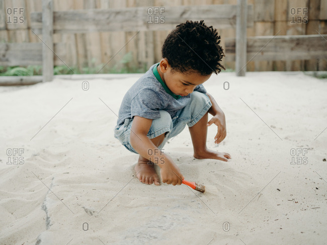 adorable African American boy in casual outfit playing with dry sand while spending time in yard on sunny day
