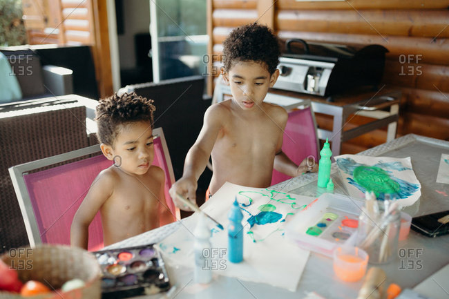 Two shirtless African American boys using bright paint to make abstract pictures on table at home