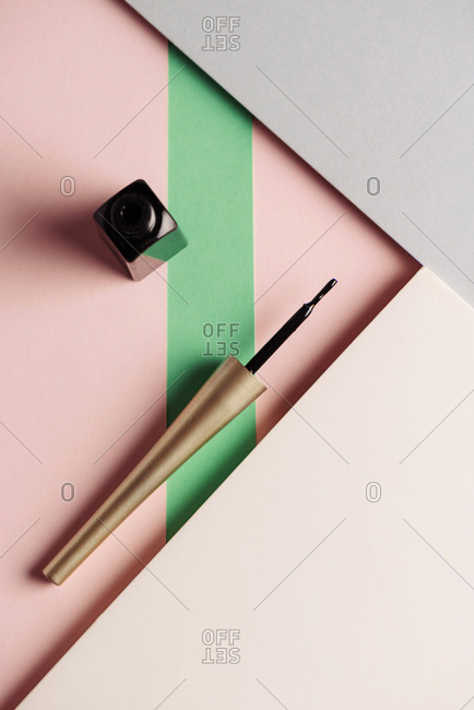 Liquid eyeliner brush, on attractive background, of pastel pink and green colors. Product and makeup concept. From above