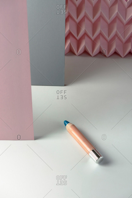 Cosmetic pencils, make up blue eyeliner pencil, modern background with pink chevron reliefs. Make up concept