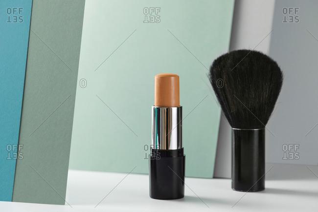 Concealer stick and make up brush on modern background