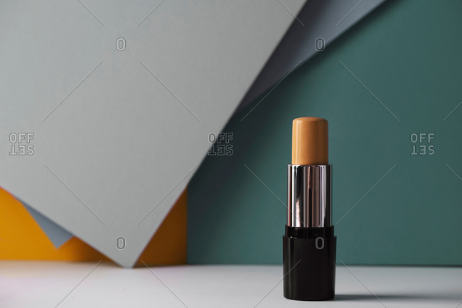 Concealer stick on modern background with geometric shapes.
