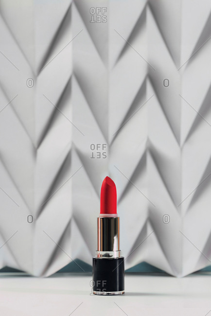 Pink lipstick on raised white chevron. Product and make up contemporary concept