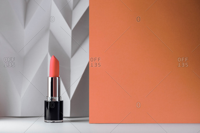 Living coral lipstick white chevron background and copy space for text. Product and make up contemporary concept.