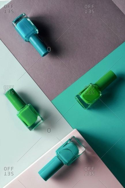 Multi-colored nail polish on pastel colors geometric pattern background