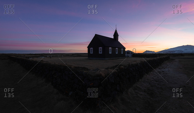 Mountains landscape with black wooden Christian church Budakirkja in Iceland