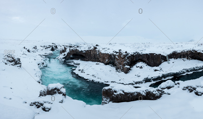 Magnificent view of powerful stream of water reaching end of cliff and falling down in Iceland Godafoss waterfall