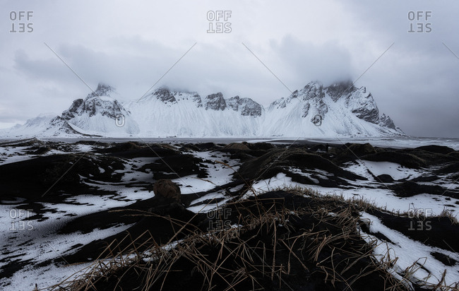 View to snowy hills with dry grass covering with mist in the morning in Stockness Iceland