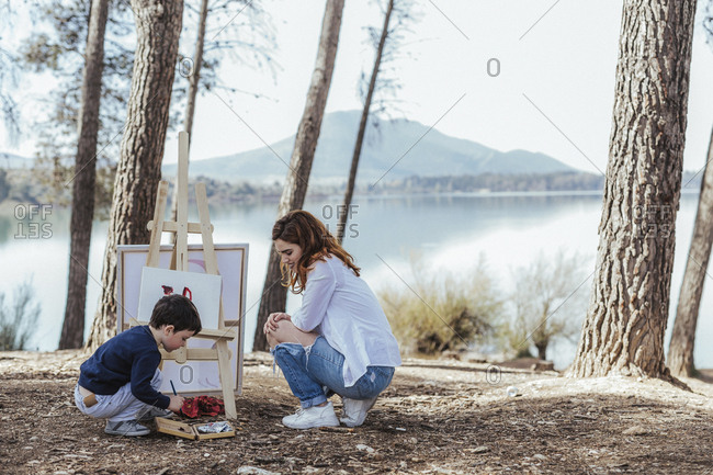 Side view of pretty female sitting on haunches and looking at cute boy painting on easel while spending time near lake in countryside together