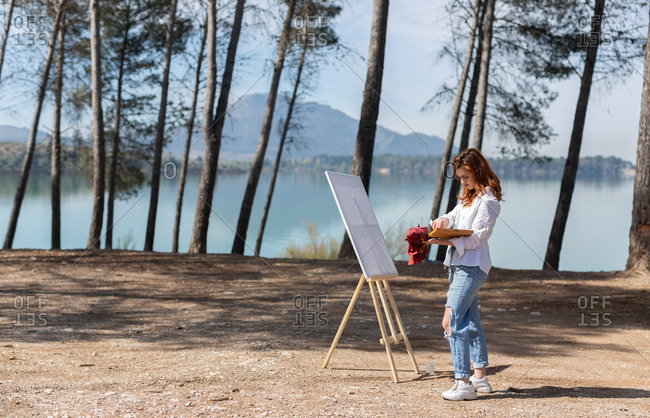 Side view of beautiful young lady in casual outfit standing near easel and painting while spending time near calm lake on sunny day in countryside