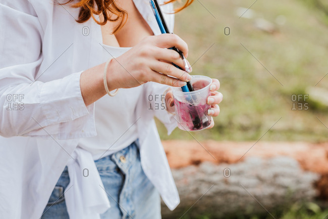 Unrecognizable female artist washing paintbrushes in small cup while painting in countryside