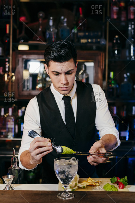 Young elegant barman working behind a bar counter mixing drinks with fruits